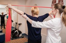 Gydytoja padeda pacientei teisingai atlikti pratimą