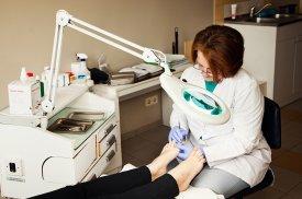 Gydytoja atlieka higieninį pedikiūrą pacientei