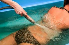 Pacientei atliekamas povandeninis masažas