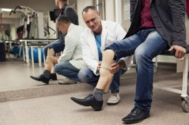 Gydytojas pacientui parodo individualiai pagamintą protezą