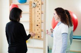 Gydytoja aiškina pacientei kaip teisingai atlikti pratimus