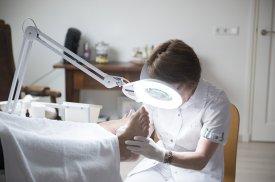 Gydytoja atlieka pacientės pėdų apžiūrą
